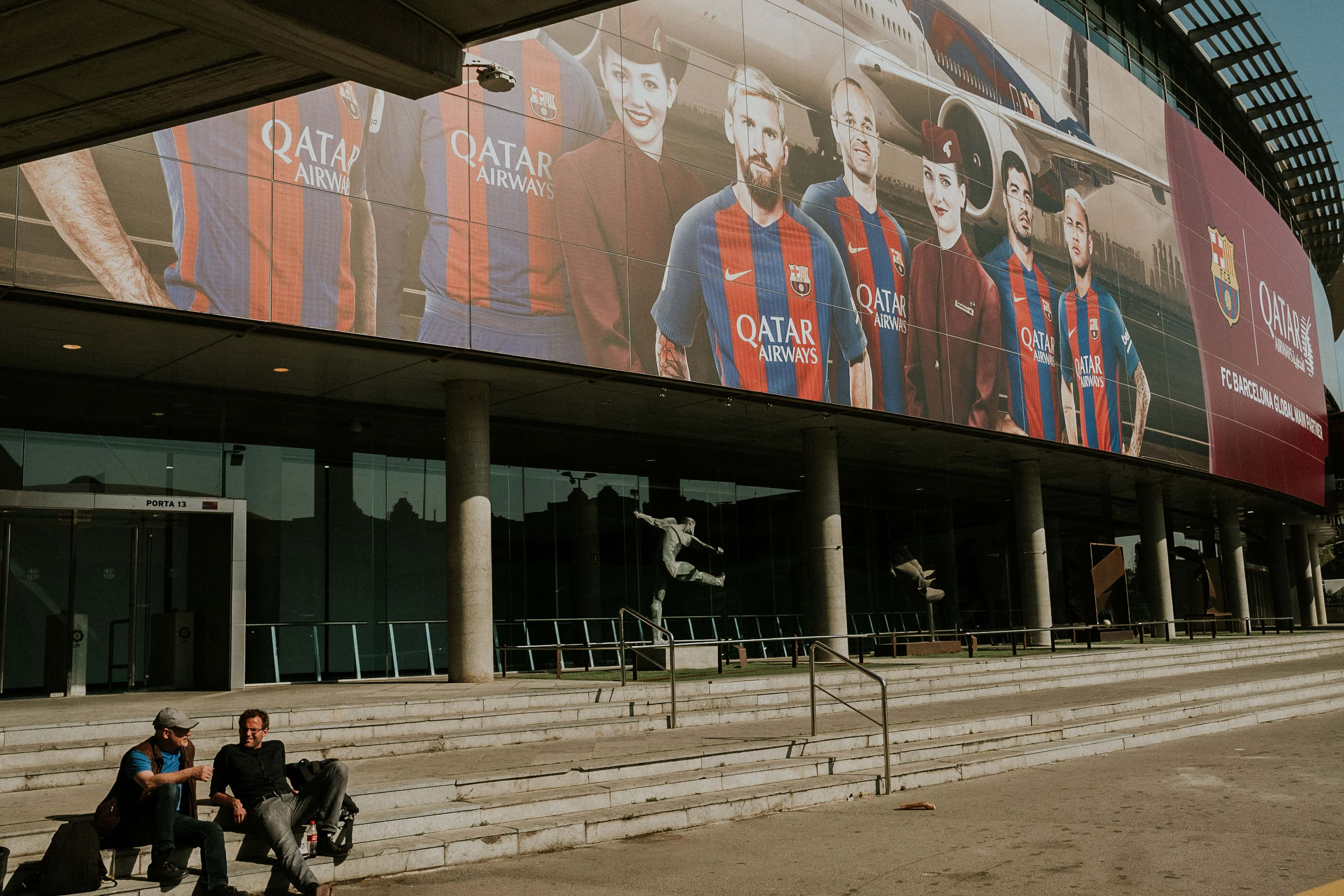 Two men lounging on the steps of Camp Nou