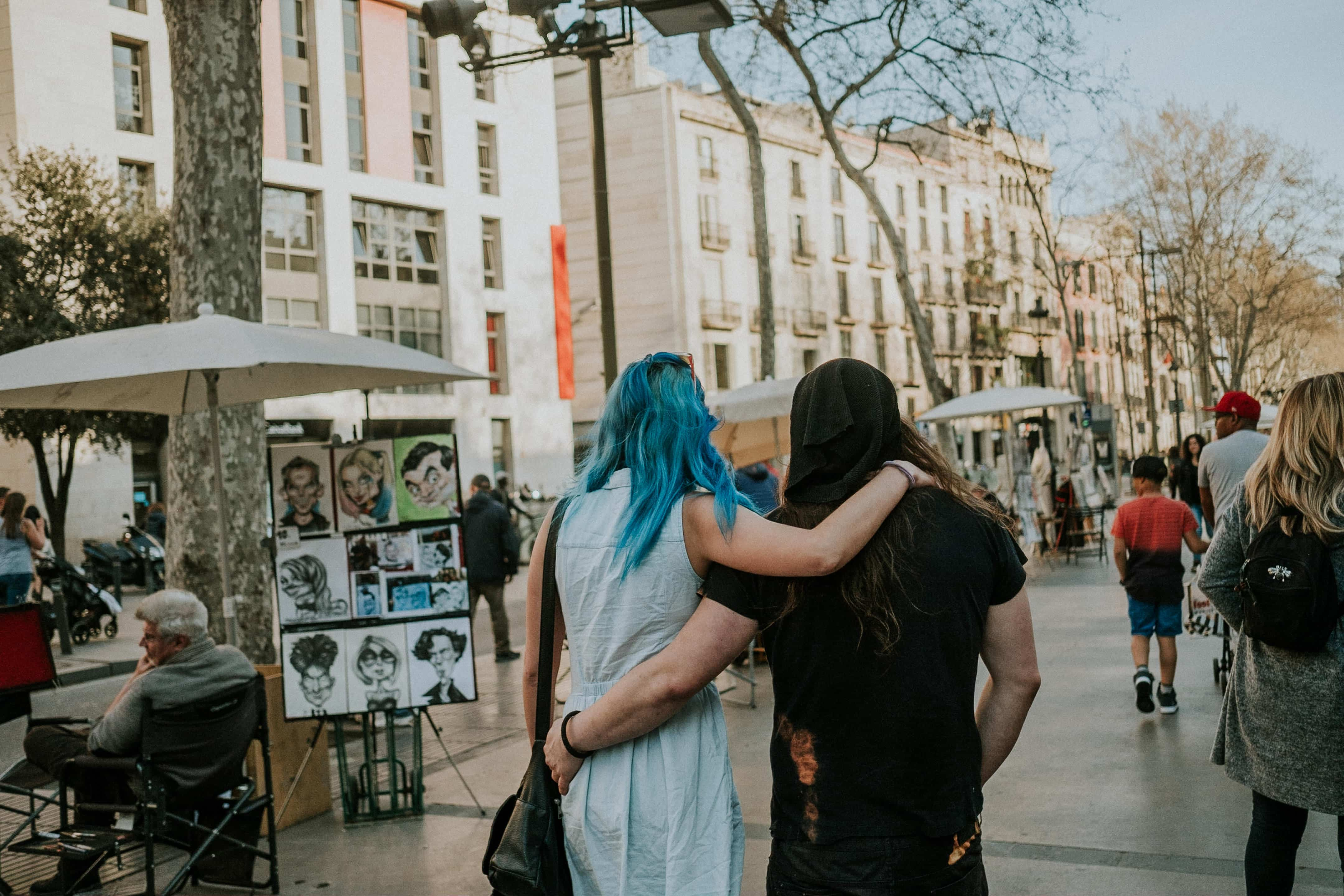 A young couple embracing as they walk down Las Ramblas, Barcelona