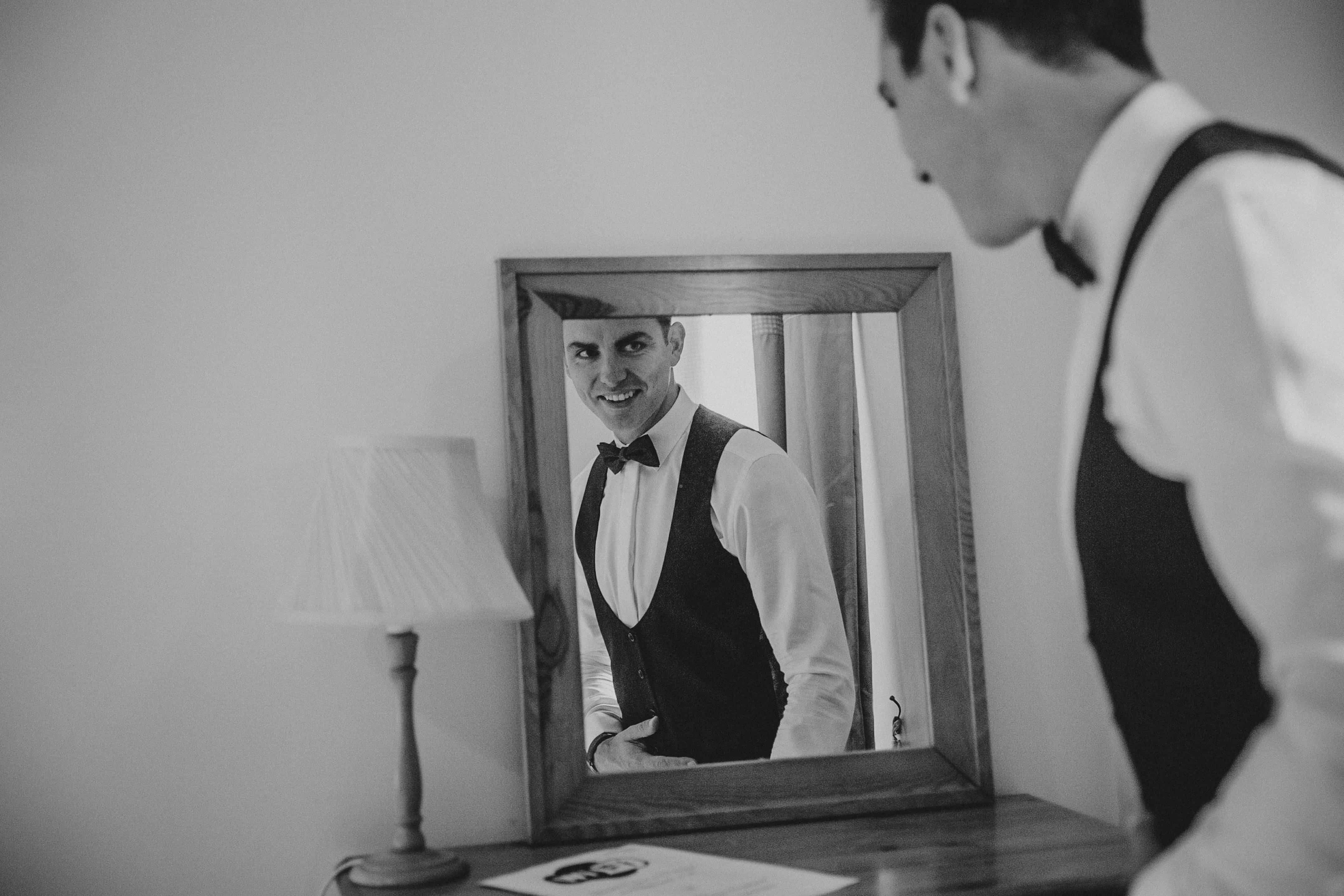 Groom looks in the mirror