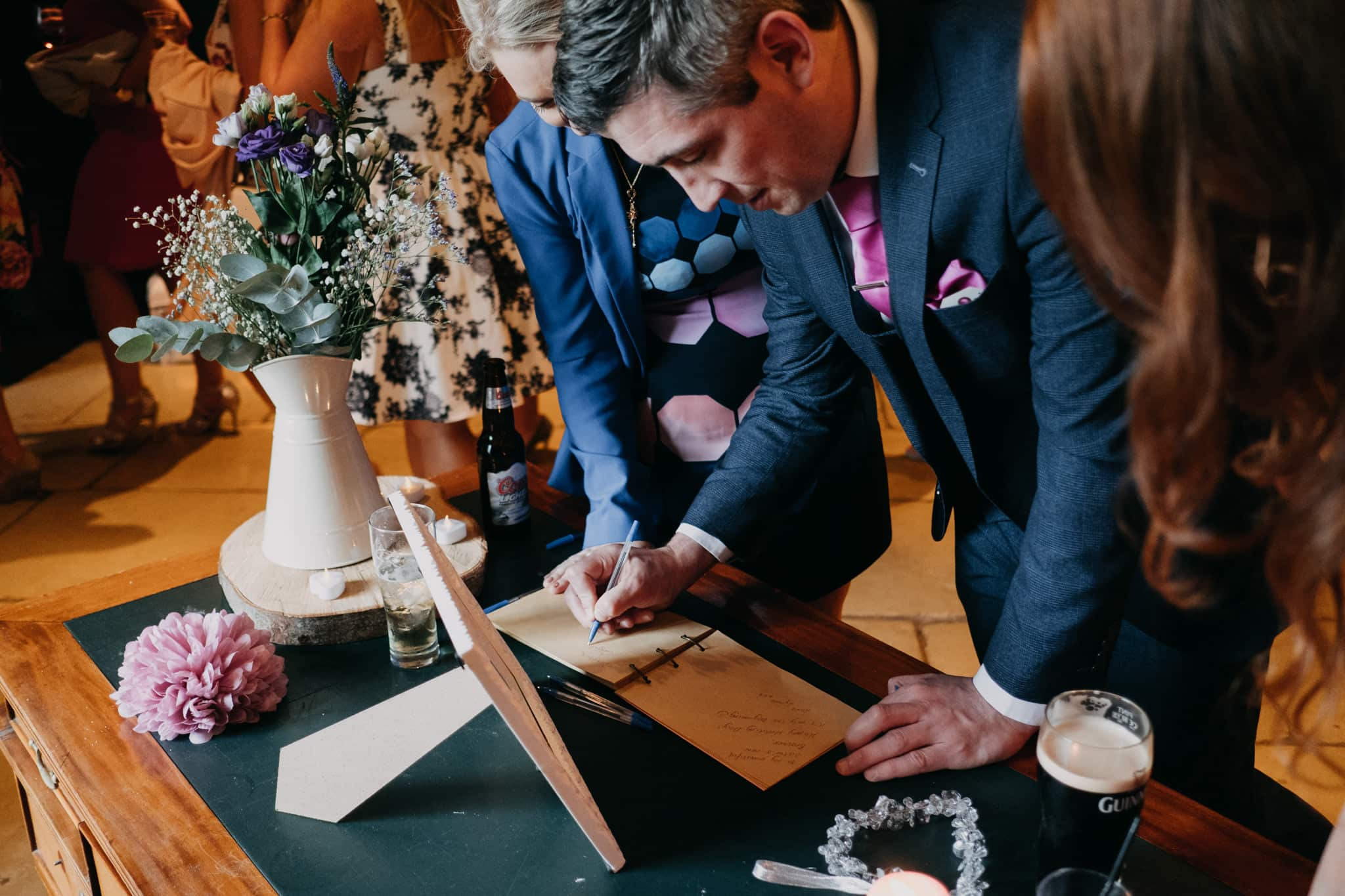 wedding guests sign the guest book