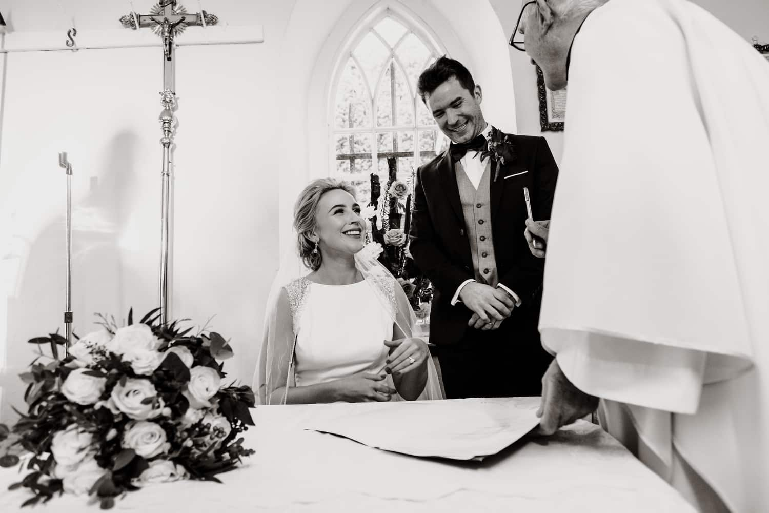 bride and groom laugh as they sign register