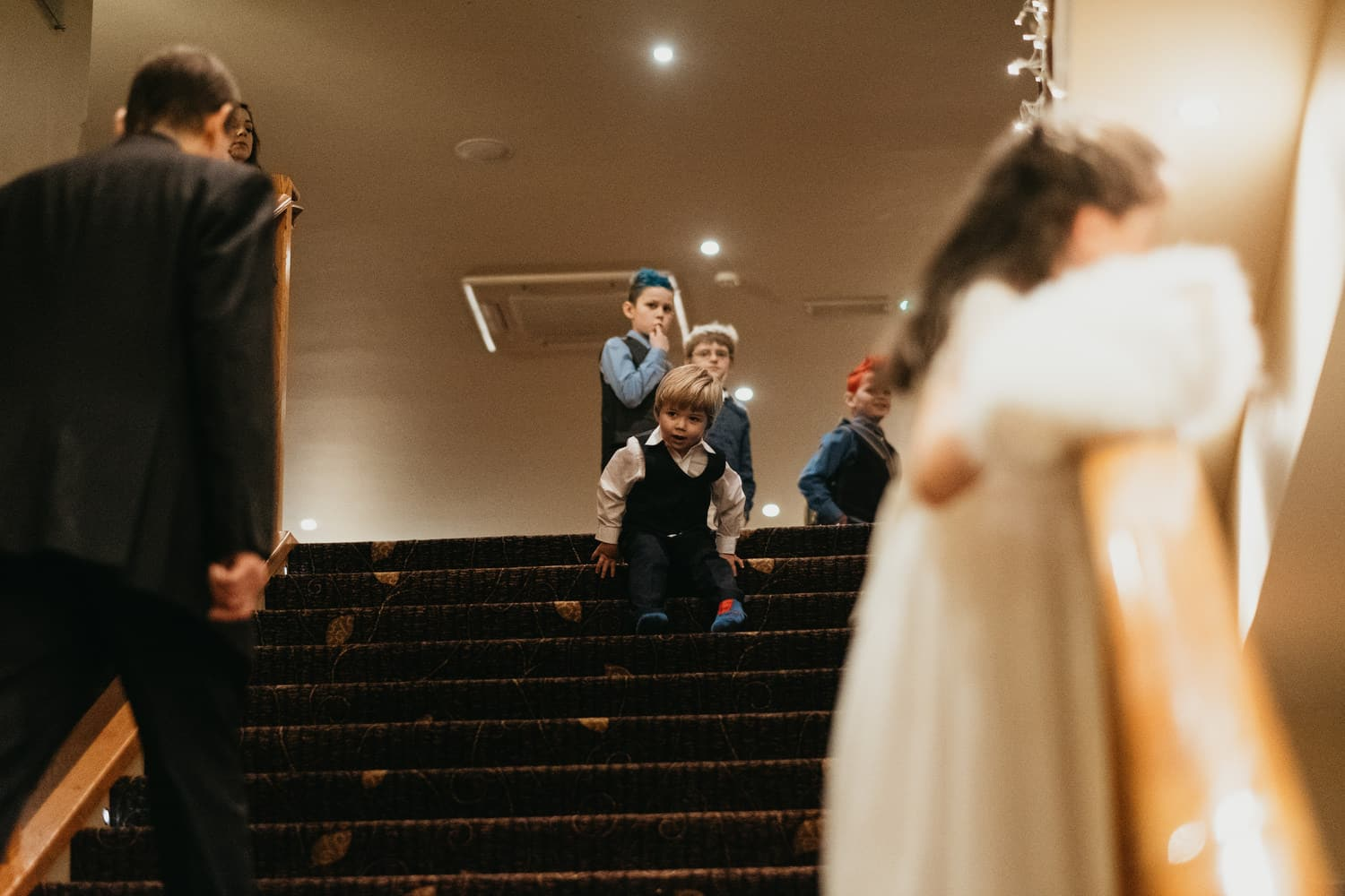 kids play on the stairs at wedding reception