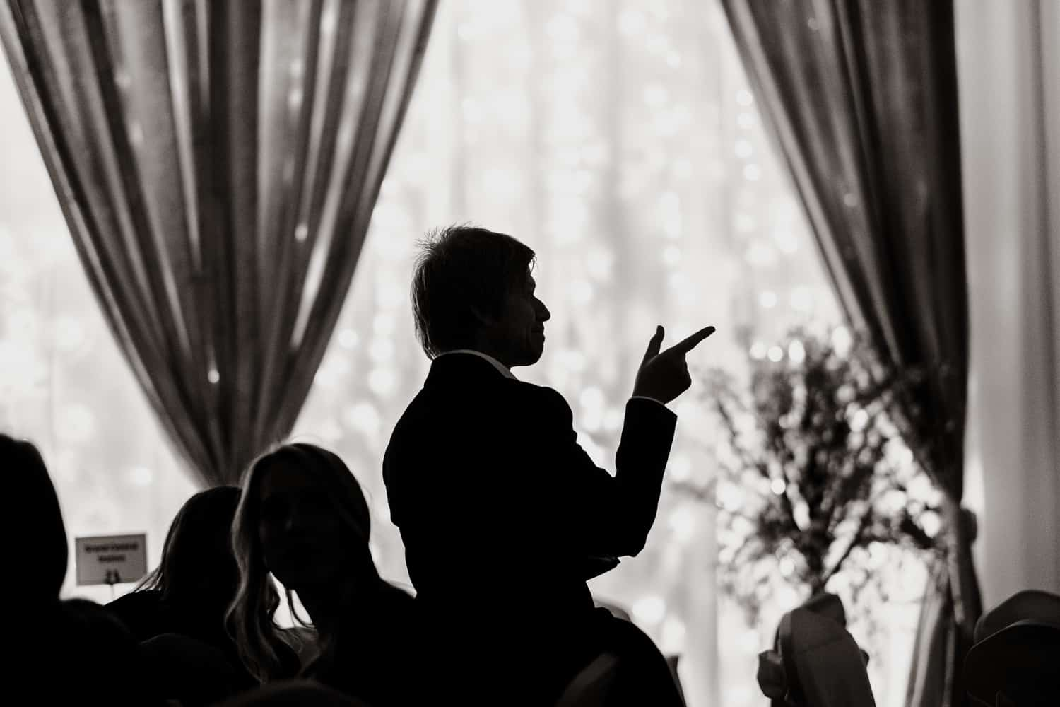 silhouette of a wedding guest pointing his finger