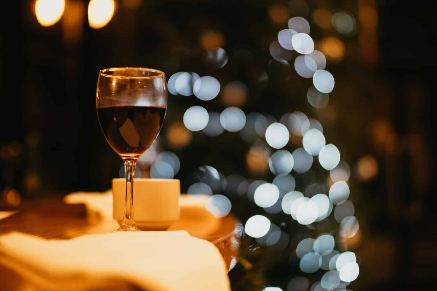 a glass of wine with a christmas tree in the background