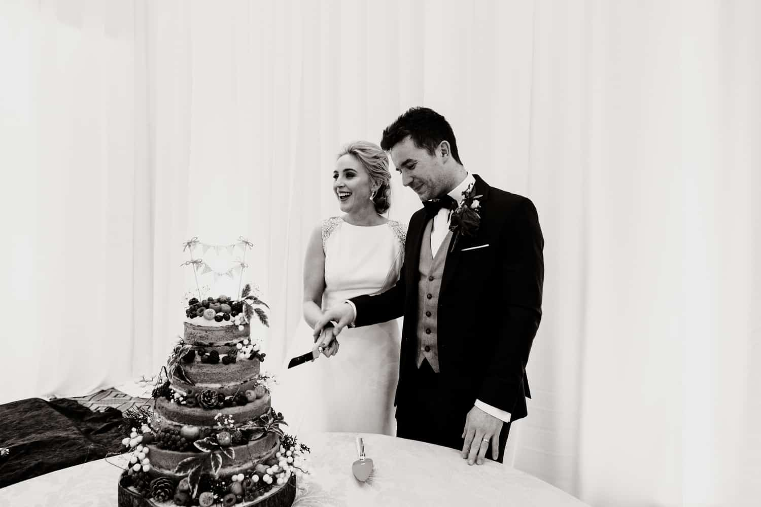 candid photograph of bride and groom cutting cake